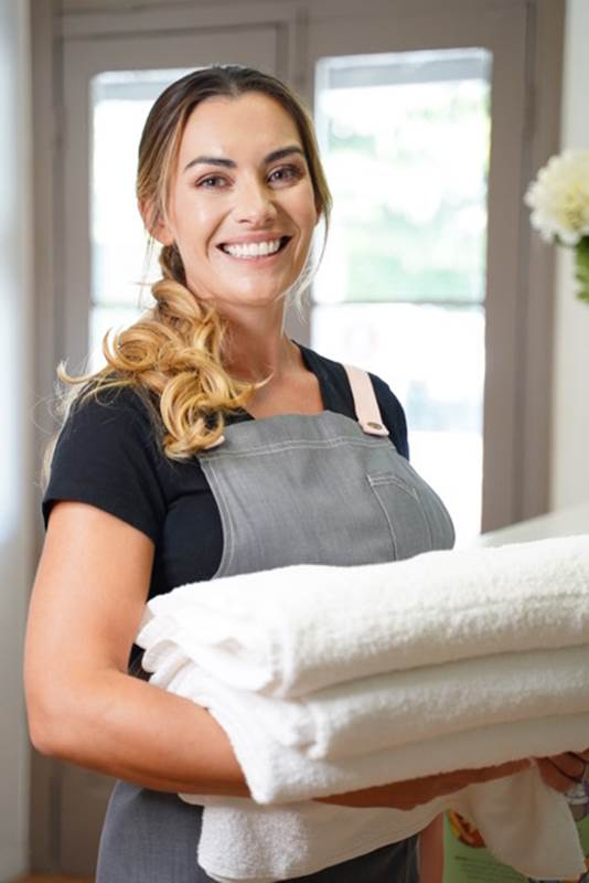 Therapist Linsey carrying towels at West Ave Beauty, Wynnum
